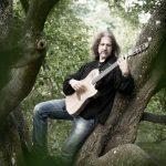 Mand spiller guitar i skoven