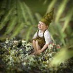 Dreng i alfetøj i skovbunden
