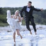Brudepar hopper op i luften ved vandkanten