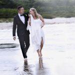 Brudepar i vandkanten smiler til hinanden