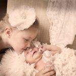 Nyfødt baby ligger i kuffert, og ved siden af storesøster