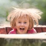 Barn springer op ad træstamme