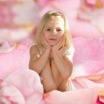 Pige i en bunke rosenblade