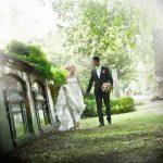 Brudepar går langs gammel slotsmur hånd i hånd