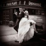 Nygifte posere som filmstjerne foran en bil