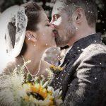 Nygift par kysser mens der kastes med ris