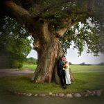 Lykkeligt brudepar op ad et træ i naturen