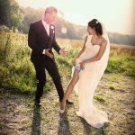 Lykkelig brudepar på eng smiler til hinanden