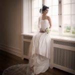 Brudt hvid kjole sidder i vindueskarm og smiler